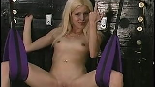 Small-titted blonde in swing plays with her twat